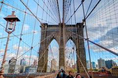 NEW YORK, OKT, 25, 2013: Ansicht über berühmtes NYC-Brooklyn-Brücken-Tor und gehende Leutetouristen Berühmte New- Yorkbrückenarch Lizenzfreie Stockbilder