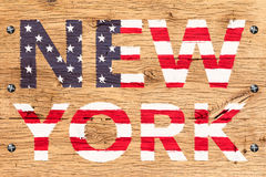 New York painted with pattern of flag United States old oak wood. New York text painted with pattern of flag United States. Painting is colorful on old oak wood stock photo