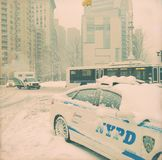 New York Police Department and bus in New York City during a snowstorm Stock Photo