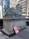 New York Public Library Main Branch, Fortitude, Library Lion, NYC, NY, USA. Protest signs from the March for Our Lives placed near `Fortitude,` one of the two stock image