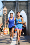 New York runners running on Brooklyn bridge NYC. New York runners running training on Brooklyn bridge NYC during busy rush hours with tourists. Fit young couple royalty free stock images