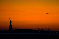 New York's Statue of Liberty at sunset. The Statue of Liberty and a passenger jet stand silhouetted at sunset Royalty Free Stock Photo