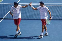 Grand Slam champions Mike and Bob Bryan of United states in action during US Open 2017 round 3 men`s doubles match. NEW YORK -SEPTEMBER 4, 2017: Grand Slam Stock Image