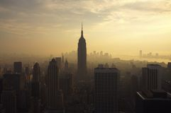 New York Skyline at dusk. Dusk light illuminates the New York Cite Skyline. Pollution adds an ornage mist into the distance and the Empire State Builing sits stock image