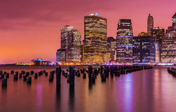New York skyline at night with varicolored reflections in the water, USA Royalty Free Stock Photos