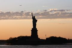 Background for postcard Statue of Liberty in New York city. New York skyline and statue of freedom with the flight of a plane above it stock images