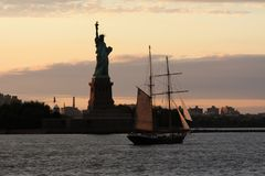 Background for postcard Statue of Liberty in New York city. New York skyline and statue of freedom with a sailing ship in the background stock photos