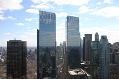 New York Skyscrapers small twin towers. Shot taken from a rooftop. Reflecting the buildings around them. A winter shot with blue sky and light fluffy clouds Royalty Free Stock Photography