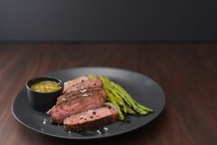 New york steak with asparagus on black plate with pesto