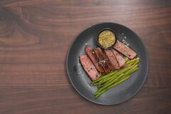 New york steak with asparagus on black plate with pesto top view