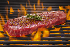 New York Steak on Flaming Hot Grill Royalty Free Stock Photo