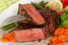 New York Steak- meat on Green Beans,Carrot,Pepper Stock Images