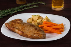 New York Steak. A perfectly cooked New York steak served with carrots and potatoes on a white plate with a beer royalty free stock image