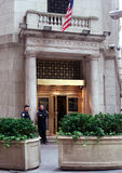 New York stock exchange entrance. One of the entrances to the New York Stock Exchange on Wall Street, a stone facade with an elegant metal door. Two policemen or Royalty Free Stock Photo
