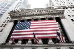 New York Stock Exchange. New York, NY: August 27, 2016: Flag draped NYSE on Wall Street. The New York Stock Exchange NYSE is the largest stock exchange in the Stock Image