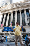New York Stock Exchange. New York, NY: August 27, 2016: Happy man holding $20 bills in front of the NYSE. The New York Stock Exchange NYSE is the largest stock Stock Images