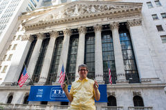 New York Stock Exchange. New York, NY: August 27, 2016: Man holding $20 bills in front of NYSE on Wall Street. The New York Stock Exchange NYSE is the largest Royalty Free Stock Image