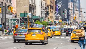 New York, streets. High buildings, cars and cabs. USA, New York, Manhattan streets. May 2, 2019. Skyscrapers, signs and ads, cars and taxi cabs stock images