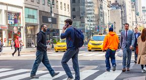 New York, streets. High buildings and people walking. USA, New York, Manhattan streets. May 2, 2019. Skyscrapers, cars and people crossing the street royalty free stock image