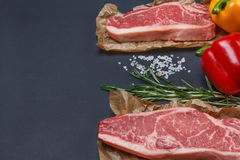 New York striploin Steak with pepper, salt and rosemary backgr Stock Photo