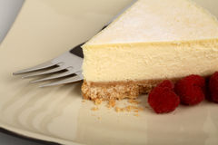 New York style cheesecake. On a plate with raspberries Royalty Free Stock Photo