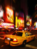 New York Taxi in Times Square. One of the famous yellow cabs in New York speeding through Times Square, the theater and entertainment district, at midnight royalty free stock images