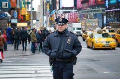 NEW YORK TIMES FYRKANT, OKTOBER 25 2013: Man för den New York polisDeparmen polisen i svart likformig som går på gatan med folk o royaltyfri bild