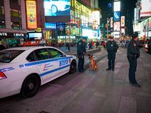 NEW YORK TIMES SQUARE, APR,24, 2015: Times Square police officers men and beautiful police woman, police car and dog among people stock photography
