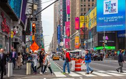 New York, Times Square. Scyscrapers, colorful neon lights, ads, cars and people. USA, New York, Times Square. May 2, 2019. High modern buildings, colorful neon stock photography