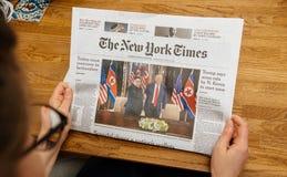 The New York Times about Trump Kim meeting summet singapore. PARIS, FRANCE - JUNE 13, 2018: Woman reading The New York Times newspaper in the office showing on stock photography