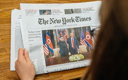 The New York Times about Trump Kim meeting summet singapore. PARIS, FRANCE - JUNE 13, 2018: Woman reading The New York Times newspaper in the office showing on royalty free stock images
