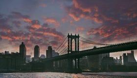 Manhattan bridge night view, cloudy sky. New York town, Manhattan bridge overcast day, night view with red clouds Stock Photos