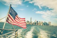 New York und Manhattan-Skyline und -amerikanische Flagge Stockfotos