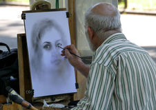 NEW YORK, UNITED STATES - AUGUST 25TH, 2016: An artist sketches a woman in Central Park on a summer day. NEW YORK, UNITED STATES - AUGUST 25TH, 2016: An artist Royalty Free Stock Image