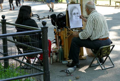NEW YORK, UNITED STATES - AUGUST 25TH, 2016: An artist sketches a woman in Central Park on a summer day. NEW YORK, UNITED STATES - AUGUST 25TH, 2016: An artist Royalty Free Stock Photos