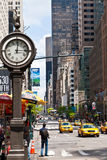 New York urban city life with taxis passing by 5th avenue and a big street clock. Royalty Free Stock Image