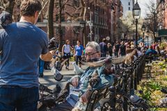 NEW YORK, USA - APRIL 14, 2018: An elderly man feeding pigeons in a park near with the West Village in New York. stock image
