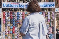 NEW YORK USA - APRIL 14, 2018: En försäljare som säljer anti--trumf politiska knappar i en parkera i New York City, arkivfoto