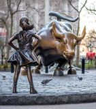 The Fearless Girl statue facing Charging Bull in Lower Manhattan, New York City. New York, USA - April 9, 2017 - The Fearless Girl statue facing Charging Bull in royalty free stock photos