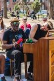 NEW YORK USA - APRIL 14, 2018: Män som nära sjunger och spelar pianot i parkera med den västra byn, New York royaltyfri fotografi