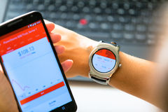 New York, USA - August 20, 2015: Business woman looking a the stock quotes on her smartwatch and smartphone Royalty Free Stock Photo