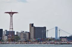 Coney Island amusement Park with attractions and crowded beach. View from ocean. royalty free stock photos