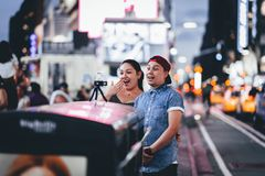 New York, USA - August 3, 2018: Young couple smiling and taking selfie in Time Square royalty free stock photo