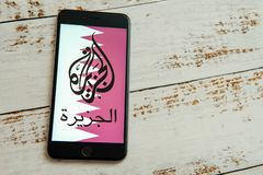 Black iPhone with logo of news media Al Jazeera on the screen. royalty free stock photo