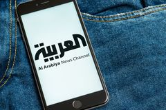 Black phone with logo of news media Al Arabiya on the screen. royalty free stock image