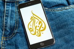Black phone with logo of news media Al Jazeera on the screen. stock photos