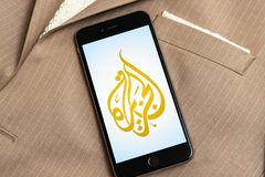 Black phone with logo of news media Al Jazeera on the screen. stock images