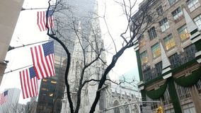 NEW YORK, USA - DECEMBER, 2017: Cathedral and skyscrapers in fog, view from bottom, american flags on the building. Manhattan stock video footage