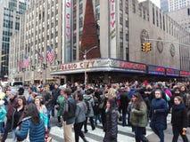 New York USA, December 3, 2016: Folk som framme korsar gatan av radiostadsmusik Hall royaltyfri fotografi