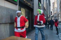 NEW YORK, USA - 10. Dezember 2011 - Leute gekleidet als Weihnachtsmann, der Weihnachten feiert Lizenzfreie Stockfotografie
